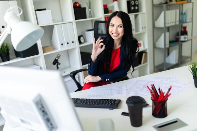 Hermosa joven sentado en el sillón en la mesa blanca en la oficina y mostrando signo bien.