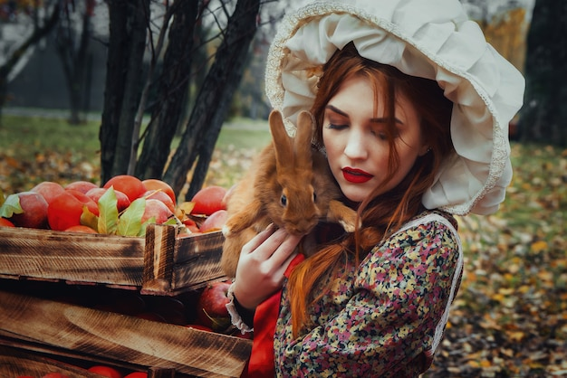 Hermosa joven sexy con manzanas rojas en jardín de otoño
