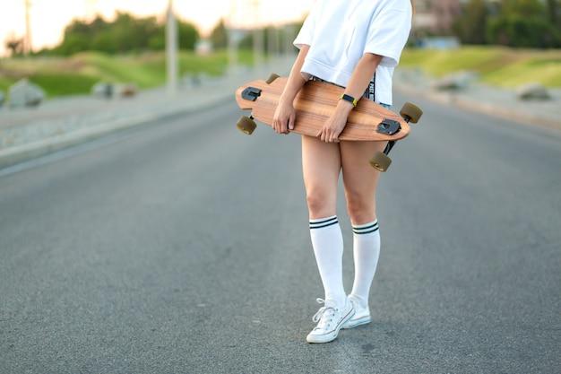 Hermosa joven sexy en shorts muy cortos caminando con longboard en tiempo soleado. ocio. estilo de vida saludable. deportes extremos. look de moda, retrato hipster al aire libre, bali, zapatillas de deporte, hipster, sunse