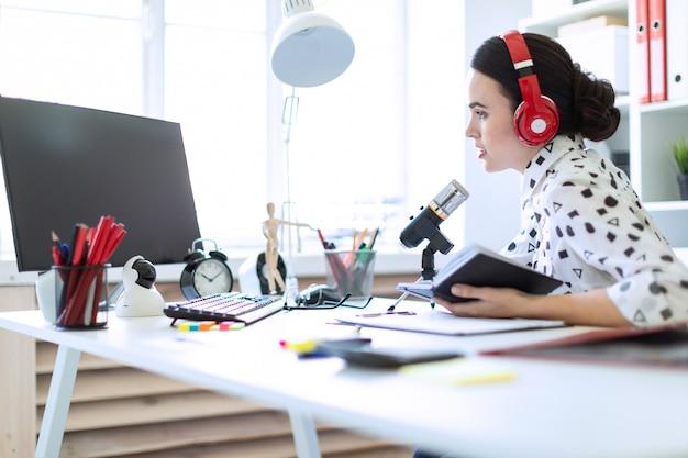 Hermosa joven se sienta en auriculares y con un bloc de notas en la mesa de la oficina y habla por el micrófono.
