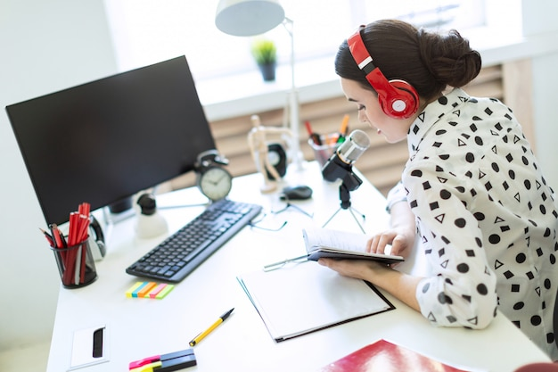 La hermosa joven se sienta en los auriculares y con una libreta en la mesa de la oficina y habla por el micrófono.