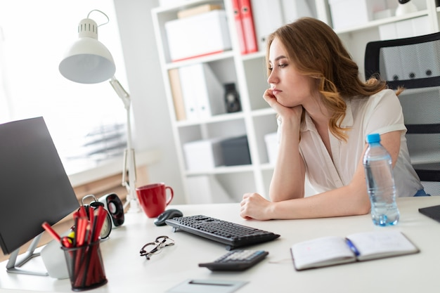 Hermosa joven se sienta en la oficina y mira el monitor.