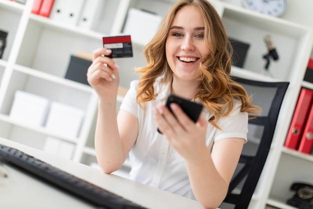 Hermosa joven se sienta en la oficina, tiene una tarjeta bancaria y un teléfono en la mano.