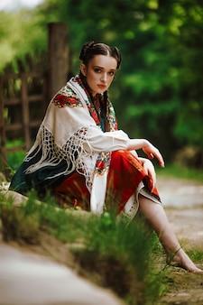 Hermosa joven se sienta en un parque con un colorido vestido ucraniano
