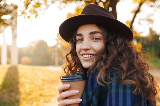 Hermosa joven con sombrero caminando en el parque en otoño, sosteniendo una taza de café para llevar