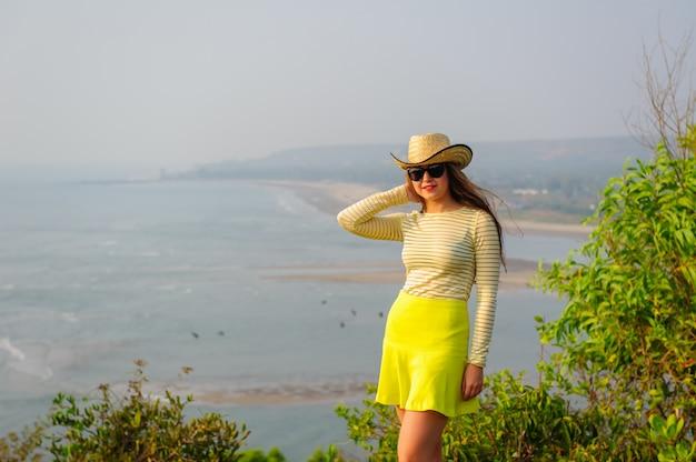 Hermosa joven con sombrero de paja, gafas oscuras y falda corta amarilla se encuentra en la parte superior contra la costa y la playa en bruma