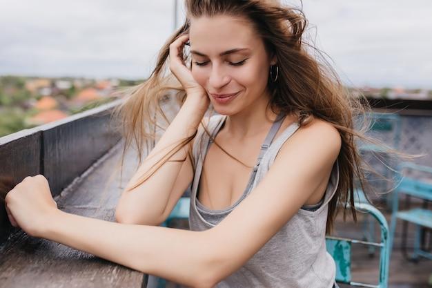 Hermosa joven soñadora posando en fin de semana de primavera. modelo femenino atractivo con el pelo largo y oscuro sentado en el techo con los ojos cerrados.