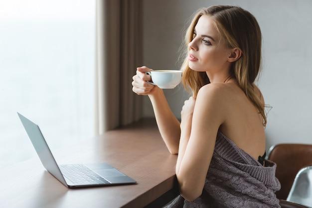 Hermosa joven soñando con laptop bebiendo café y mirando por la ventana