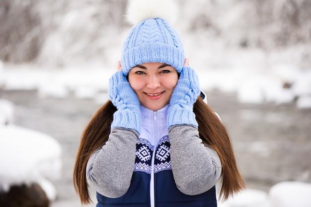 Hermosa joven sonriendo y jugando con nieve en invierno