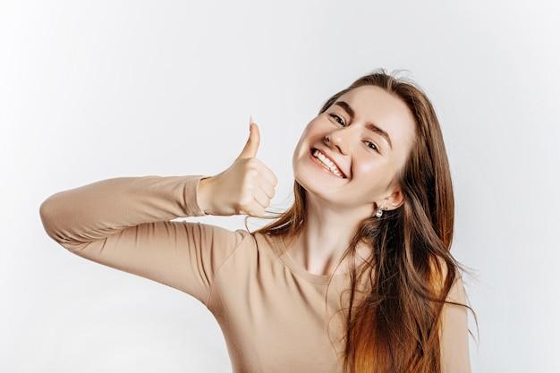 Hermosa joven sonriendo y muestra los pulgares para arriba gesto sobre un fondo blanco aislado. una mujer señala una idea, un lugar para publicidad. morena positiva con un jersey beige.