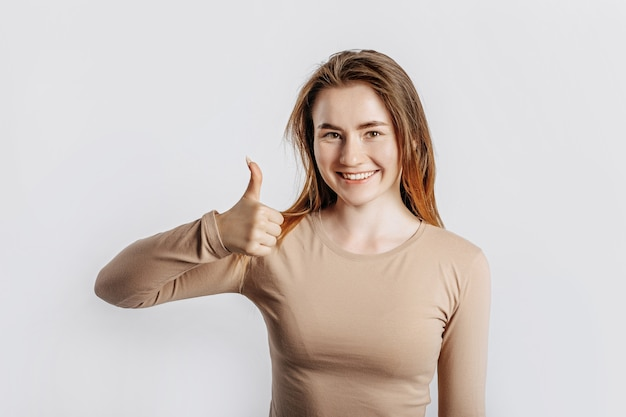 Hermosa joven sonriendo y muestra los pulgares para arriba gesto sobre fondo blanco aislado