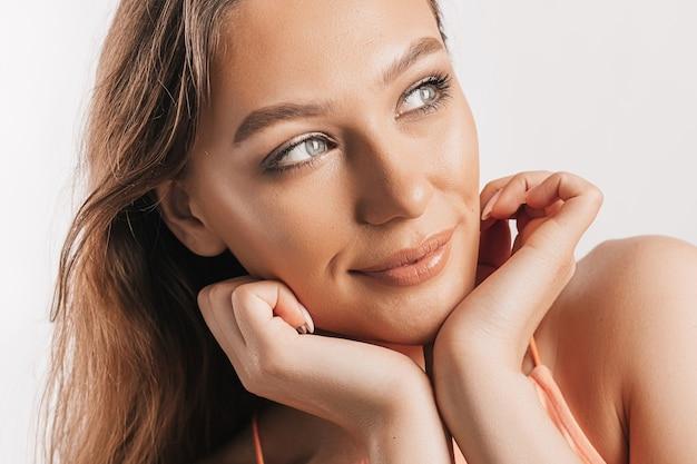 Hermosa joven sonriendo y posando mirando a la cámara sobre un fondo blanco aislado. mujer morena positiva. mirada amable. rostro de belleza.