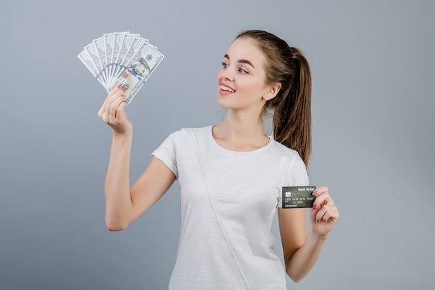 Hermosa joven sonriendo y sosteniendo billetes de cien dólares y tarjeta de crédito aislado sobre gris