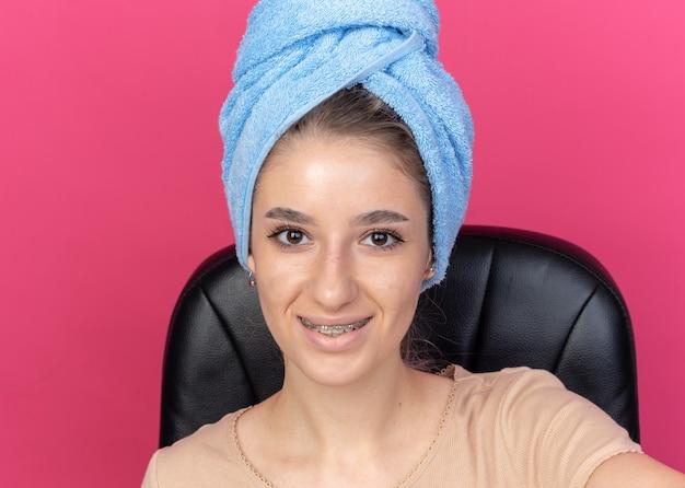 Hermosa joven sonriente con aparatos dentales envuelto el cabello en una toalla sosteniendo la cámara aislada sobre fondo de color rosa