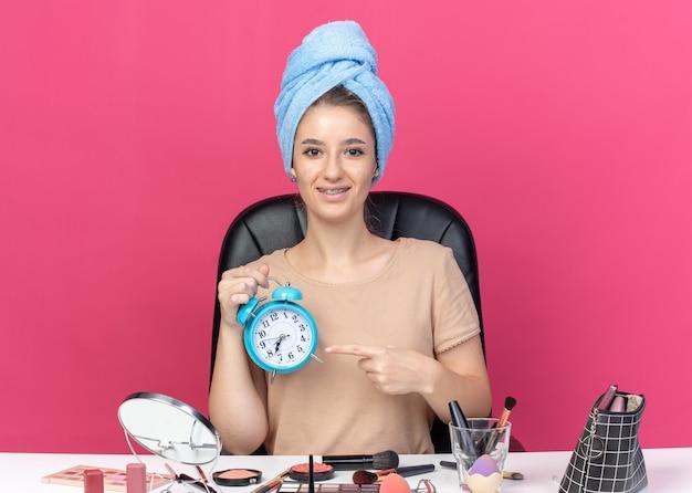 Hermosa joven sonriente con aparatos dentales se sienta a la mesa con herramientas de maquillaje envuelto en el pelo con una toalla sosteniendo y apunta al despertador aislado sobre fondo rosa