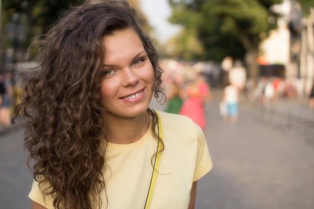 Hermosa joven sonriente con cabello rizado y camiseta amarilla para pasear por la ciudad