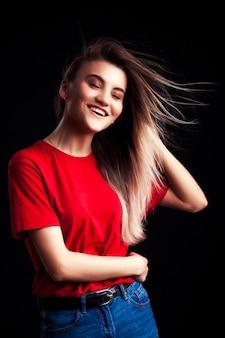 Hermosa joven sonriente en camiseta roja y jaens posando con las manos en la cadera