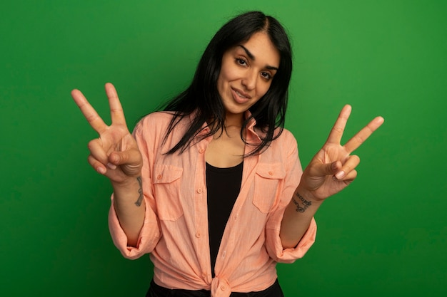 Hermosa joven sonriente con camiseta rosa mostrando gesto de paz aislado en la pared verde