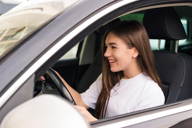 Hermosa joven sonriente conduciendo un coche en la carretera