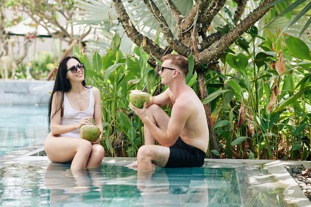 Hermosa joven sonriente disfrutando de un cóctel de coco y escuchando una interesante historia de su novio