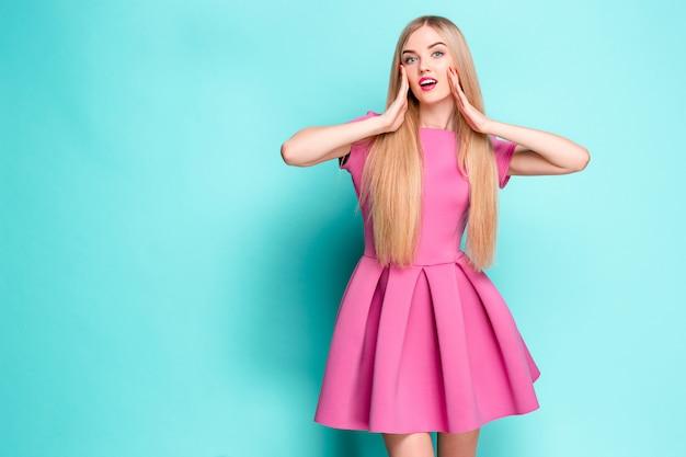 Hermosa joven sonriente en mini vestido rosa posando en el estudio