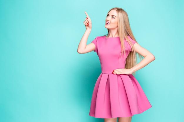 Hermosa joven sonriente en mini vestido rosa posando, presentando algo