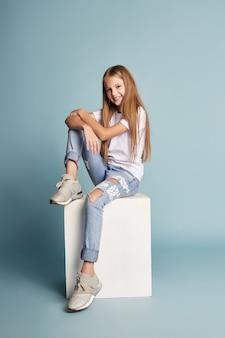 Hermosa joven sonriente sentada en un cubo