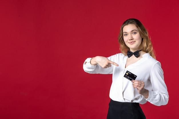 Hermosa joven sonriente servidor femenino mariposa en el cuello y sosteniendo una tarjeta bancaria sobre fondo rojo.