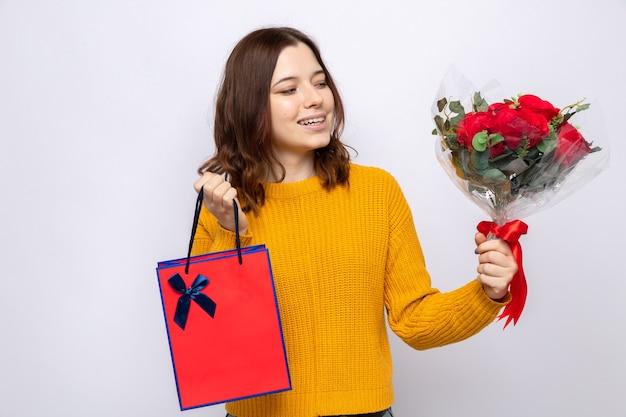 Hermosa joven sonriente sosteniendo una bolsa de regalo mirando el ramo en la mano