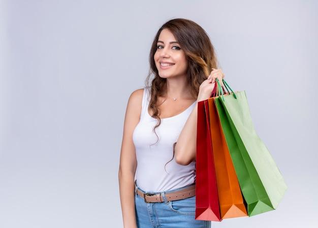 Hermosa joven sonriente sosteniendo bolsas de la compra.