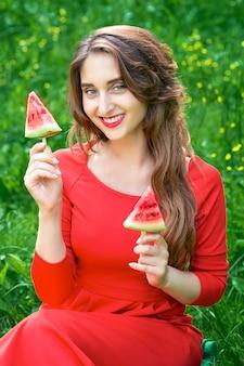 Hermosa joven sonriente está sosteniendo una rebanada de dos sandías en forma de hielo