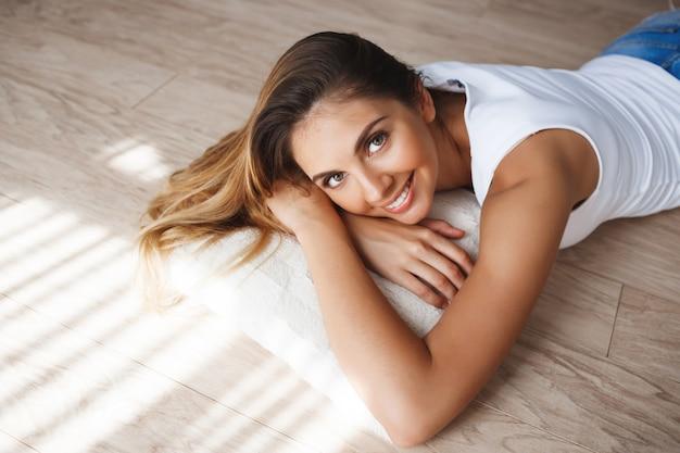 Hermosa joven sonriente vestida con camisa blanca y pantalones cortos de mezclilla acostado en el piso