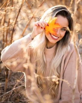 Hermosa joven soplando hojas de arce mirando a cámara