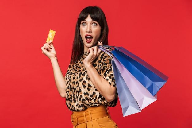 Hermosa joven sorprendida vestida con camiseta estampada de animales posando aislada sobre pared roja con tarjeta de crédito y bolsas de la compra.