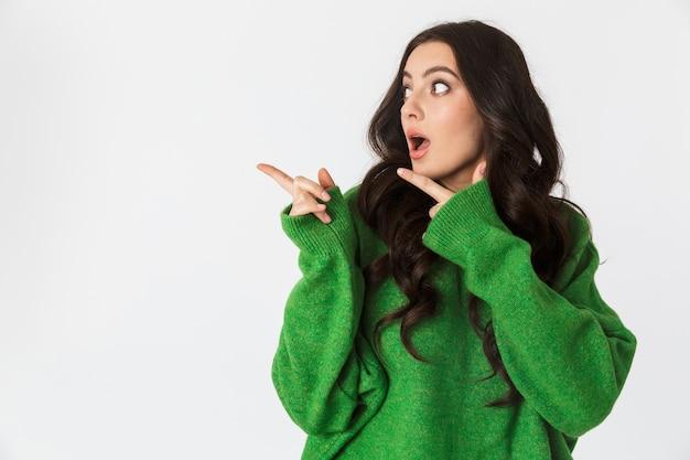 Hermosa joven sorprendida vestida con suéter verde posando aislado en la pared blanca apuntando.