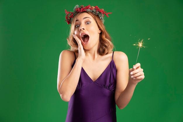 Hermosa joven sorprendida con vestido púrpura con corona sosteniendo bengalas poniendo la mano en la mejilla aislada sobre fondo verde con espacio de copia