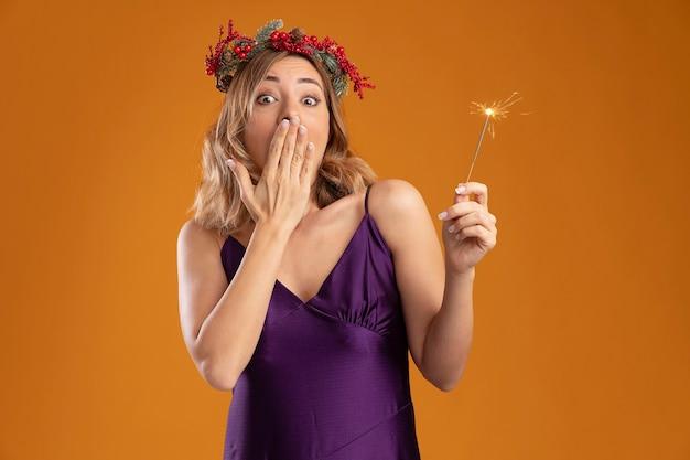 Hermosa joven sorprendida con vestido púrpura con corona sosteniendo luces de bengala cubrió la boca con la mano aislada sobre fondo marrón
