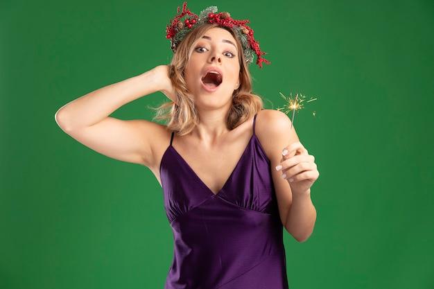 Hermosa joven sorprendida con vestido púrpura con corona sosteniendo luces de bengala poniendo la mano en la cabeza aislada sobre fondo verde