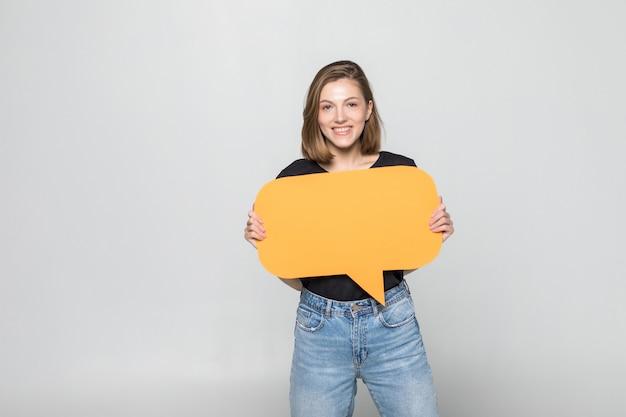 Hermosa joven sosteniendo bocadillo en blanco sobre pared gris