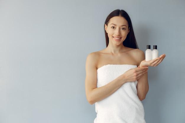 Hermosa joven sosteniendo botellas de crema