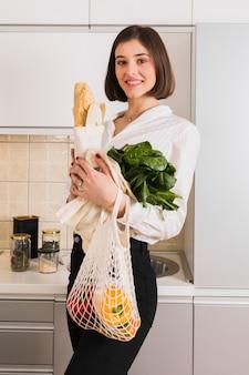 Hermosa joven sosteniendo comestibles orgánicos