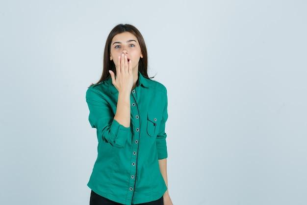Hermosa joven sosteniendo la mano en la boca con camisa verde y mirando sorprendido. vista frontal.