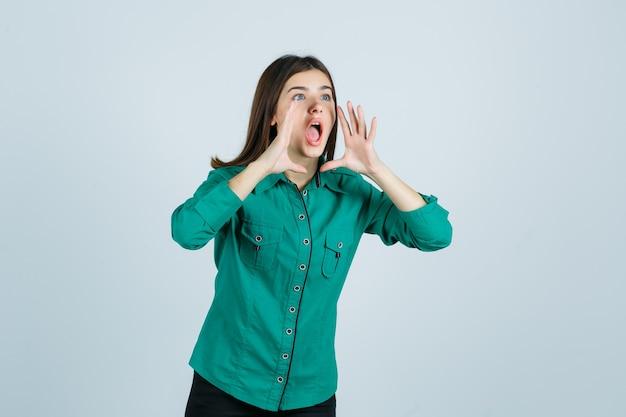 Hermosa joven sosteniendo las manos cerca de la boca mientras grita en camisa verde y mira emocionada, vista frontal.