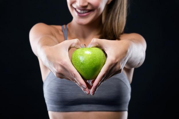 Hermosa joven sosteniendo una manzana sobre fondo negro.