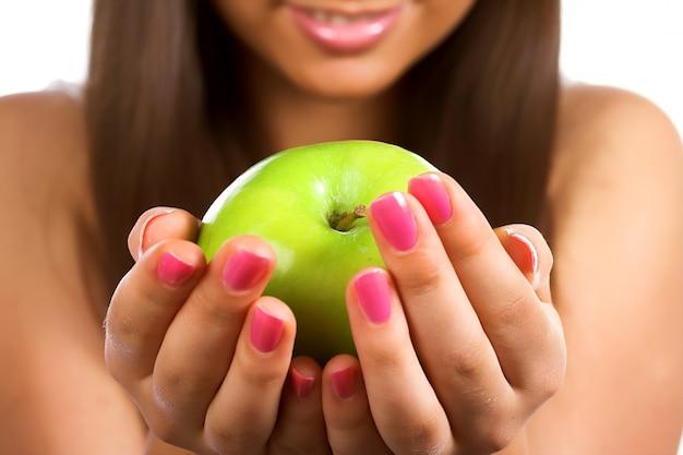 Hermosa joven sosteniendo una manzana verde