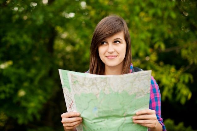 Hermosa joven sosteniendo un mapa
