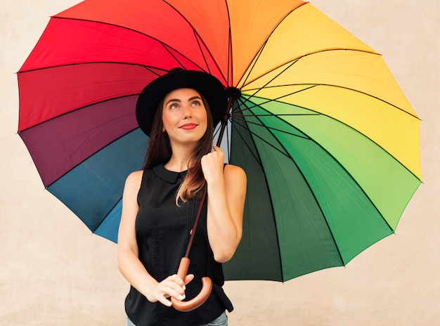 Hermosa joven sosteniendo un paraguas de arco iris