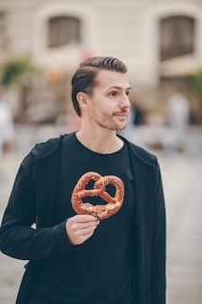 Hermosa joven sosteniendo pretzel y relajarse en el parque