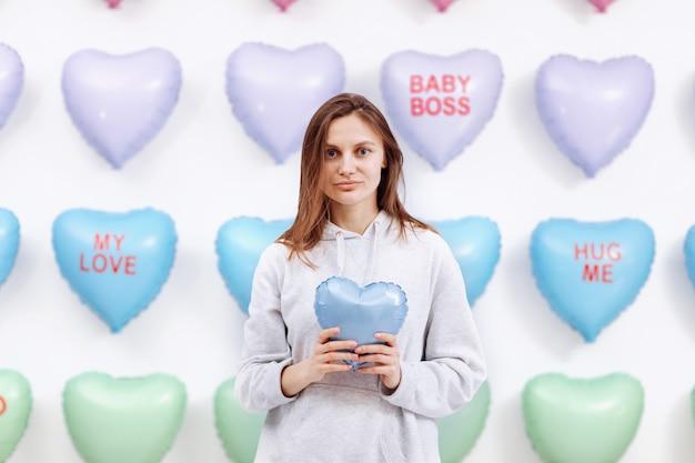 Hermosa joven sostiene el globo azul en forma de corazón. muchos corazones
