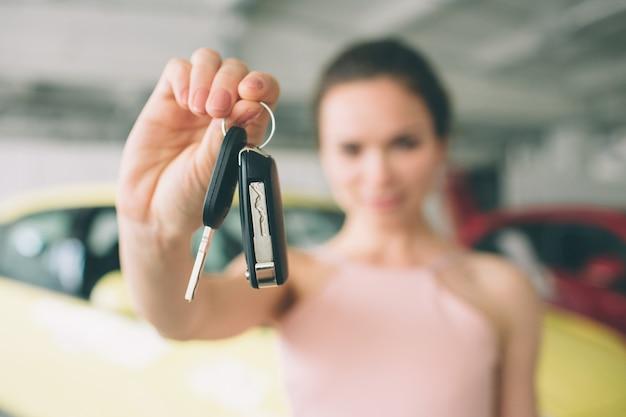 Hermosa joven sostiene una llave en el concesionario de automóviles